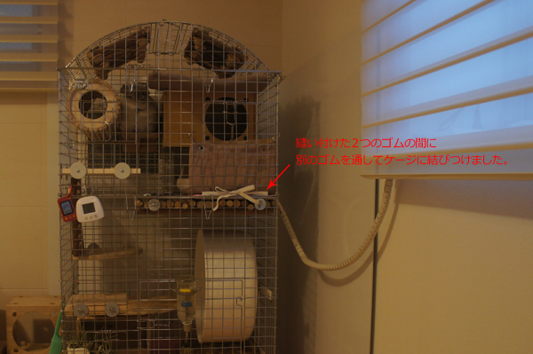 チンチラのティモの寒さ対策 ケージレイアウト さきほどのプラス工房ステージマットとマルカン リバーシブルヒーターをゴムでまとめたものを、ケージ壁面に紐を通してさらに動かないようにした様子